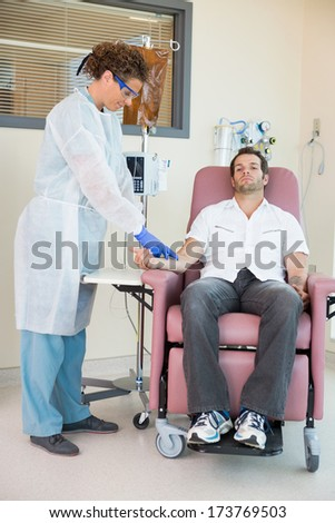 Full length of mid adult nurse injecting cancer patient during intravenous treatment in hospital room - stock photo