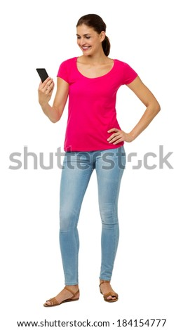 Full length of mid adult woman reading text message on smart phone against white background. Vertical shot. - stock photo