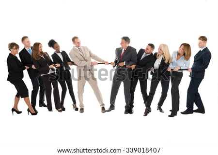 Full length of multi ethnic business teams playing tug of war against white background - stock photo