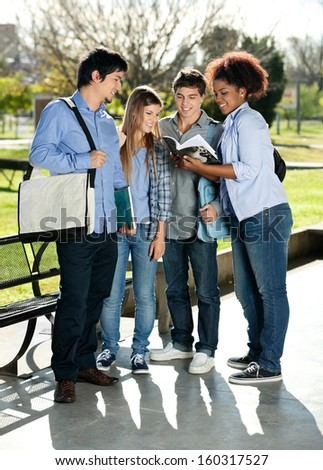Full length of multiethnic friends reading book together in college campus - stock photo