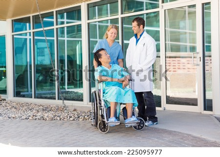 Full length of nurse and doctor looking at patient on wheelchair outside hospital building - stock photo