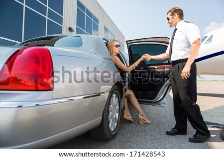 Full length of pilot helping woman stepping out of car at airport terminal - stock photo