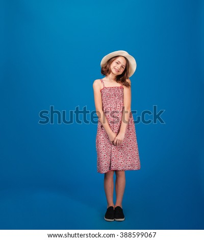 Full length of pretty cheerful little girl in sundress and hat standing and looking at camera over blue background - stock photo