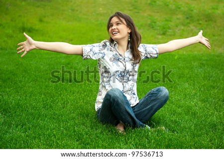 Full length of pretty young woman. Full length of pretty young woman resting on grass and smiling. Greeting with opened arms resting on grass and smiling. Greeting with opened arms - stock photo