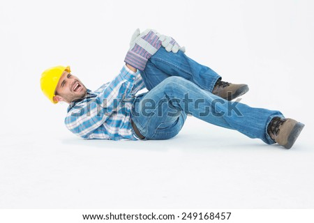 Full length of repairman suffering from knee pain while lying against white background - stock photo