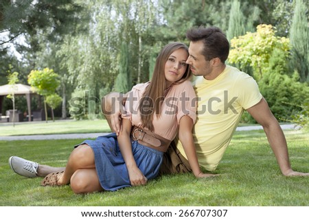 Full length of romantic young couple relaxing on grass in park - stock photo