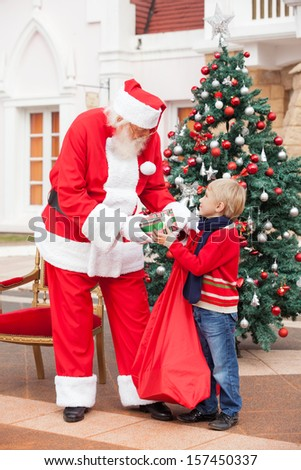 Full length of Santa Claus giving present to boy in courtyard - stock photo