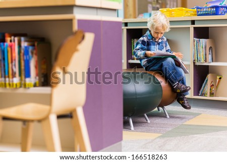 Full length of schoolboy reading book on seat in library - stock photo