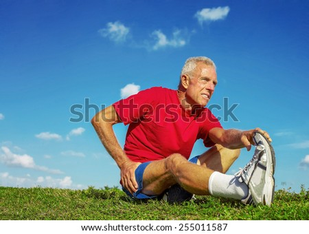 Full length of senior man in pain while stretching leg on meadow - stock photo