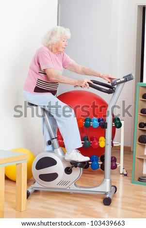 Full length of senior woman exercising on bike in gym - stock photo