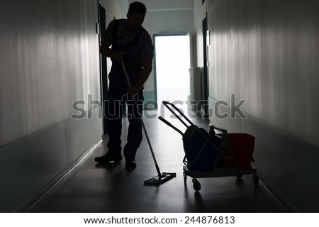 Full length of silhouette man with broom cleaning office corridor - stock photo