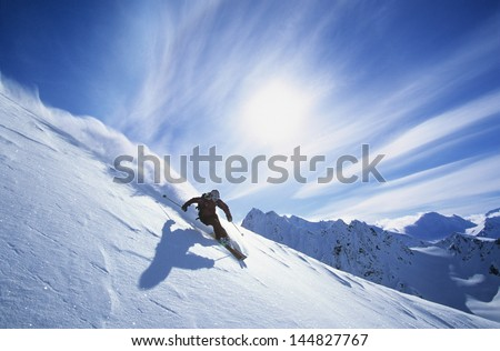 Full length of skier skiing on fresh powder snow - stock photo