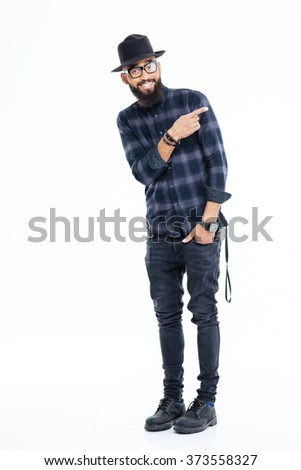 Full length of smiling bearded african man in hat and glasses standing and pointing away - stock photo
