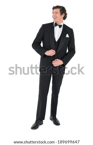 Full length of smiling groom getting ready over white background - stock photo