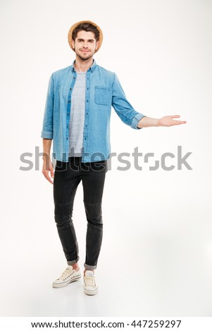 Full length of smiling handsome young man in hat holding copyspace on palm over white background - stock photo