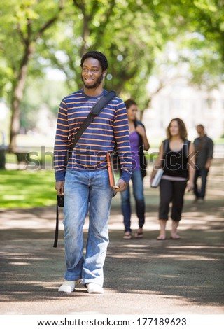 Full length of smiling male student walking on campus road with friends in background - stock photo