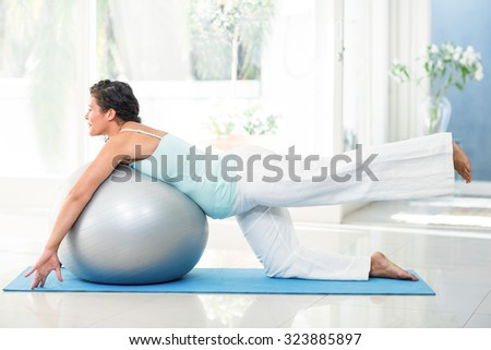 Full length of smiling pregnant woman exercising with ball on mat at fitness studio - stock photo