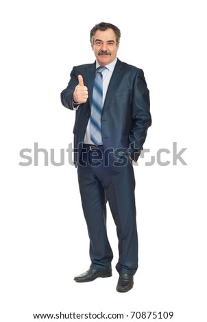 Full length of smiling senior business man giving thumb up and holding a hand into suit pocket isolated on white background - stock photo
