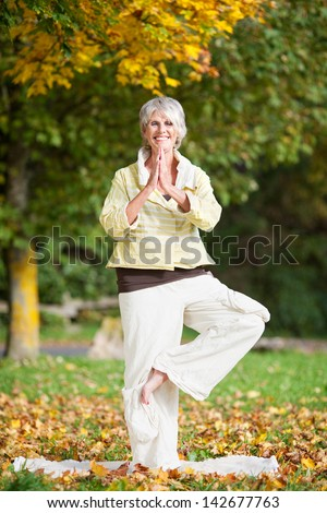 Full length of smiling senior woman with arms outstretched standing on one leg while doing yoga in park - stock photo