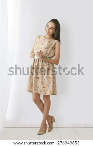 Full length of smiling young woman with coffee cup standing against white wall - stock photo