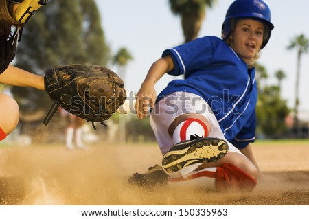 Full length of softball player sliding into home plate - stock photo