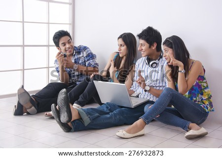 Full length of student photographing friends through camera in college - stock photo