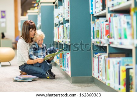 Full length of teacher and boy reading book by bookshelf in library - stock photo