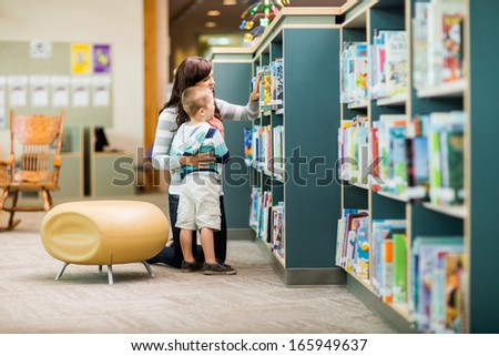 Full length of teacher and boy selecting book from bookshelf in library - stock photo
