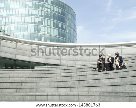 Full length of three business people sitting on steps outside office building during lunch break - stock photo