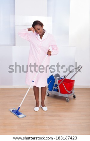 Full length of tired female housekeeper cleaning floor in hotel - stock photo