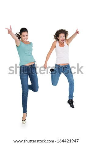 Full length of two cheerful young female friends with hand gestures over white background - stock photo