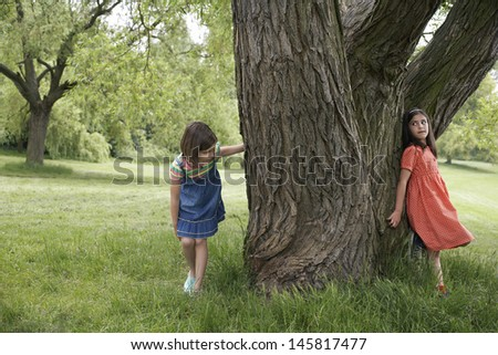 Full length of two girls playing hide and seek by tree - stock photo