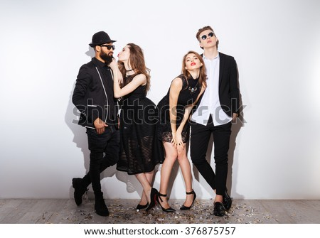 Full length of two happy drunk young couples standing over white background - stock photo