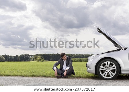 Full length of worried businessman sitting by broken down car at countryside - stock photo