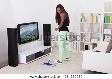Full length of young African American woman cleaning floor in living room - stock photo