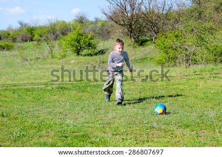 Full Length of Young Boy Enjoying Kicking Colorful Soccer Ball in Grassy Field on Sunny Day - stock photo