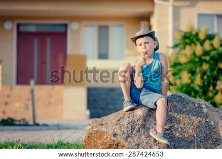 Full Length of Young Boy Outdoors in Summer Sitting on Large Boulder in front of House and Eating Ice Cream Cone - stock photo