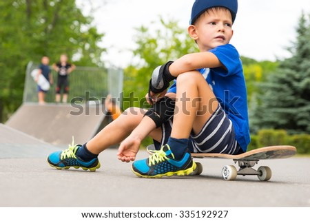 Full Length of Young Boy Taking a Break in Skate Park - Boy Sitting on Skateboard and Looking Back into the Distance in Skate Park with Other Skaters in Background - stock photo
