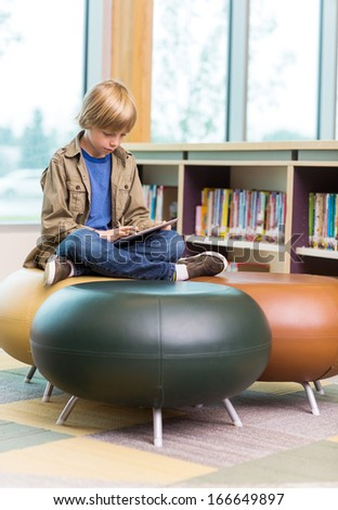 Full length of young boy using digital tablet on seat in school library - stock photo