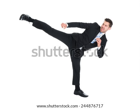 Full length of young businessman kicking over white background - stock photo