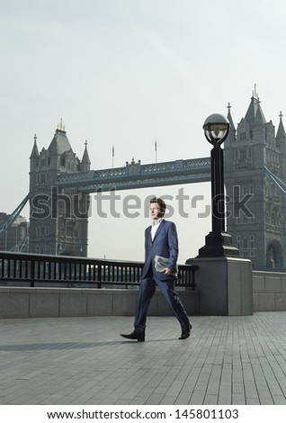 Full length of young businessman with newspaper walking in front of London Bridge - stock photo