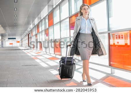 Full length of young businesswoman with luggage walking in railroad station - stock photo