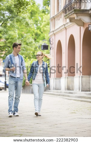 Full length of young college couple talking while walking in campus - stock photo