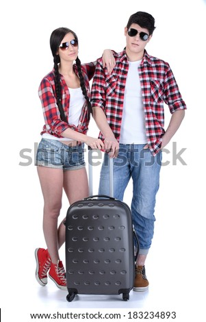Full length of young couple walking with travel suitcases, isolated on white background - stock photo