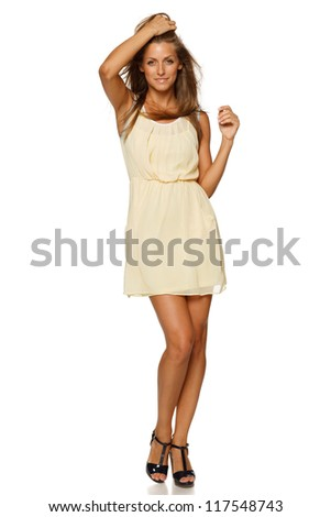 Full length of young elegant female in light yellow summer dress, over white background - stock photo
