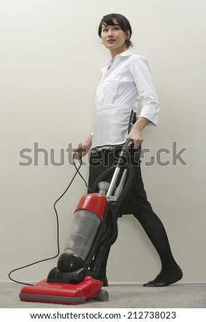 Full length of young female housekeeper vacuuming - stock photo