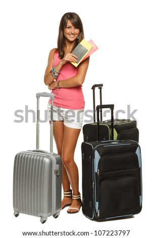 Full length of young female in casual standing with travel bags, holding passport and tickets, isolated on white background - stock photo