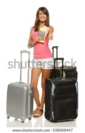 Full length of young female in casual standing with travel bags, holding passport and tickets, showing thumb up sign, isolated on white background - stock photo