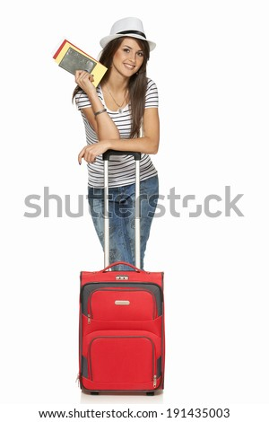 Full length of young female in casual standing with travel suitcase, holding passport and tickets, isolated on white background - stock photo