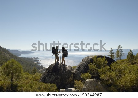 Full length of young hiking couple standing on rock at coast - stock photo